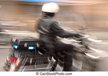 Speedy Cop - A motorcycle cop speeds by in hot pursuit of a...
