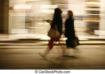 Speedy girls. - Power shopping after dark. Motion blur.