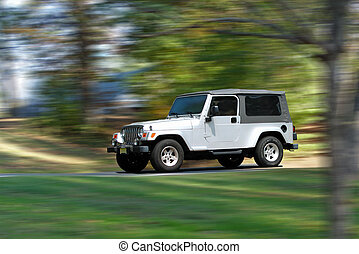 Speedy Jeep - Silver/gray jeep in motion along tree-lined...