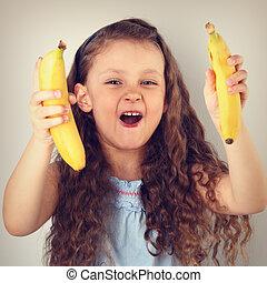 speels, lachen, vrolijke , langharige, geitje, meisje, vasthouden, en, het tonen, gele, helder, bananas., toned, ouderwetse , verticaal