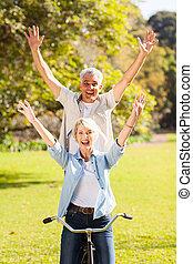 speels, senior koppel, hebbend plezier, rijdende fiets, buitenshuis