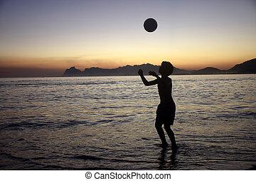 speelvoetbal op het strand, ondergaande zon