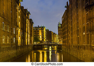 Speicherstadt in Hamburg by night with reflection in canal