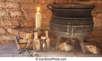 spell of witch night with candles and pot with fire between cobwebs and ancient earth