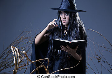 young witch holding a book casting a spell