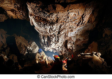Spelunker admiring beautiful stalactites in a cave