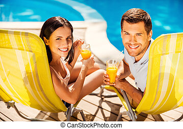 Spending carefree time poolside. Happy couple holding cocktails and smiling while sitting at the deck chairs by the pool