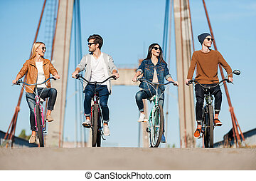 Spending carefree time together. Four young people riding...