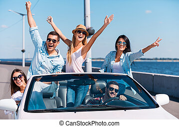 Spending great time in convertible. Group of young happy people enjoying road trip in their white convertible and raising their arms
