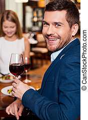 Spending great time in restaurant. Handsome young man holding glass with red wine and smiling while sitting at the restaurant with his girlfriend sitting in the background