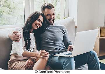 Spending great time together. Beautiful young loving couple looking at laptop and smiling while sitting together on the couch