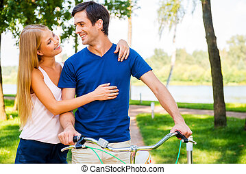 Spending great time together. Beautiful young smiling couple looking at each other and smiling while man leaning at bicycle in park