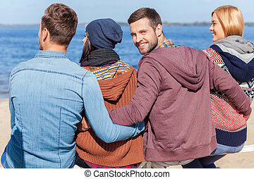 Spending great time with friends. Rear view of four young happy people enjoying time at the beach while young man looking over shoulder and smiling