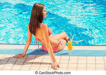 Spending summer time poolside. Rear view of young woman in bikini sitting by the poolside with cocktail near her