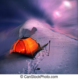 The tent is set on a hillside in winter the most beautiful and the big mountain in the Carpathians-Goverla. Moonrise brought wind and overnight becomes dangerous