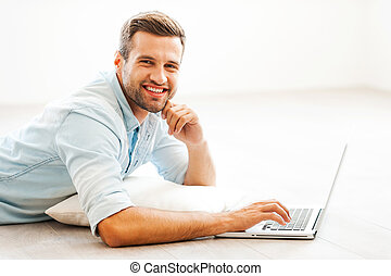 Spending time at home. Cheerful young man working on laptop and looking at camera while lying on the floor at his apartment