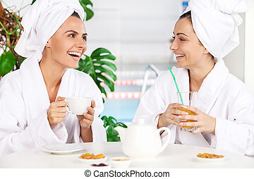 Spending time at spa. Two beautiful young women in bathrobe drinking tea and talking to each other while sitting in front of swimming pool