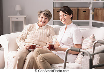 Spending time together - Happy young female carer and senior...
