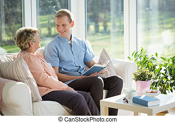 Spending time with elder woman - Male carer spending time...