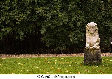 Sphinx statue standing on the grass in Lazienki park, Warsaw