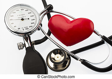 a blood pressure monitor, a heart and stethoscope lying on a white ground