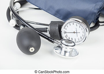 Close up of a sphygmomanometer and stethoscope laying on a white medical wor surface