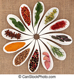 Spice and herb selection in white porcelain dishes over hessian background.