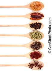 Spice collection in seven wooden spoons, isolated over white background.