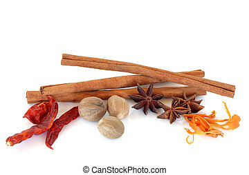 Spice selection of nutmeg, star anise, chilli, mace and cinnamon sticks, over white background.