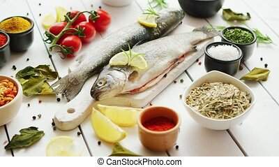 Spices and tomatoes around fish - Various aromatic spices ...