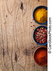 spices background: pink and black pepper, paprika powder,...