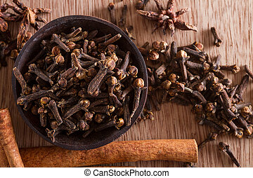 Spices series: a bowl full of cloves against a wooden background. Copy space. Star anise and cinnamon sticks on the background.
