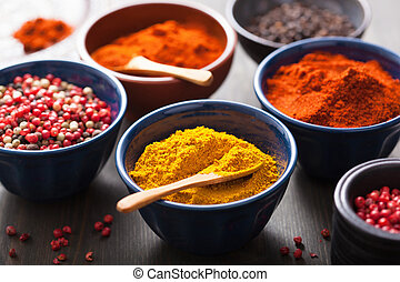 spices in bowls: curry, pink and black pepper, paprika...