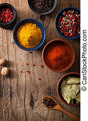 spices in bowls: pink and black pepper, paprika powder,...