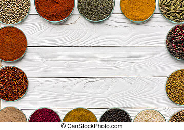spices in glass bowls on white table