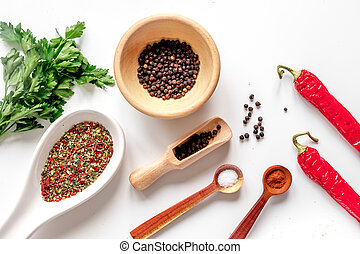 spices in wooden spoon on white background top view