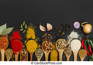 Spices in wooden spoons on black background.