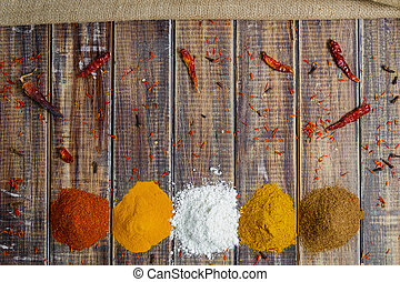 Spices near chili on wooden background. Various of spices powder selection. Frame. Top view with copy space