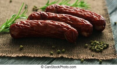 Spices near whole sausages - Twigs of fresh rosemary and...