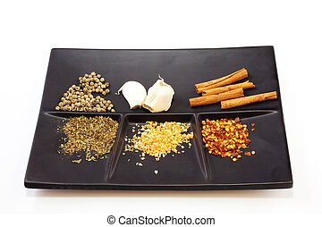 Spices on a saucer  - Different Spices on a black saucer