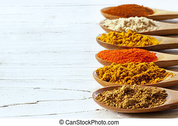 Spices on Wooden Spoons over Distressed White Timber
