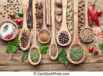 Spices with herbs on a wooden background