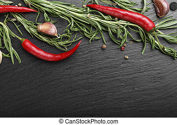 spices with hot pepper on a black background