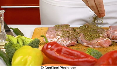 Spicing fresh raw meat in slow motion - Woman hands spicing...