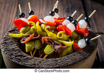 Spicy banderillas with peppers, olives and anchovies for a party