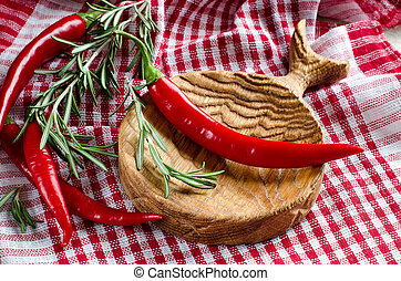 Spicy chili peppers on wooden kitchen Board