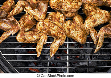 Spicy cooking chicken wings grilling on a summer barbecue...