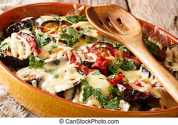 Spicy hot eggplant casserole with tomatoes, herbs and cheese close-up. horizontal