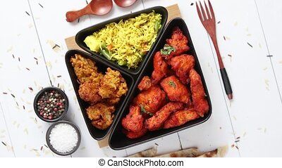 Spicy indian fried chicken served with curry vegetable rice...
