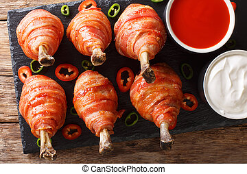 Spicy Lollipops fried chicken legs wrapped in bacon served with sauces close-up on a slate board. horizontal top view